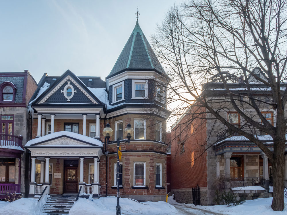 tall three story victorian home in the snow