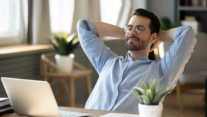 happy male-presenting office worker leaning back with eyes closed