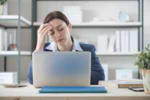 female-presenting office worker holding her head as though she has a headache